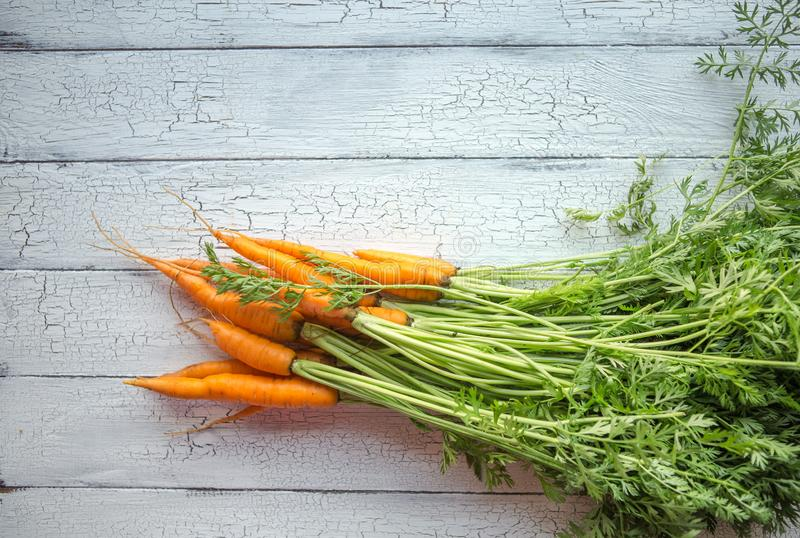 A bunch of carrots . Fresh carrots, beetroot  heap with green stems. Raw Carrots and beetroot on rustic  wooden back stock photos