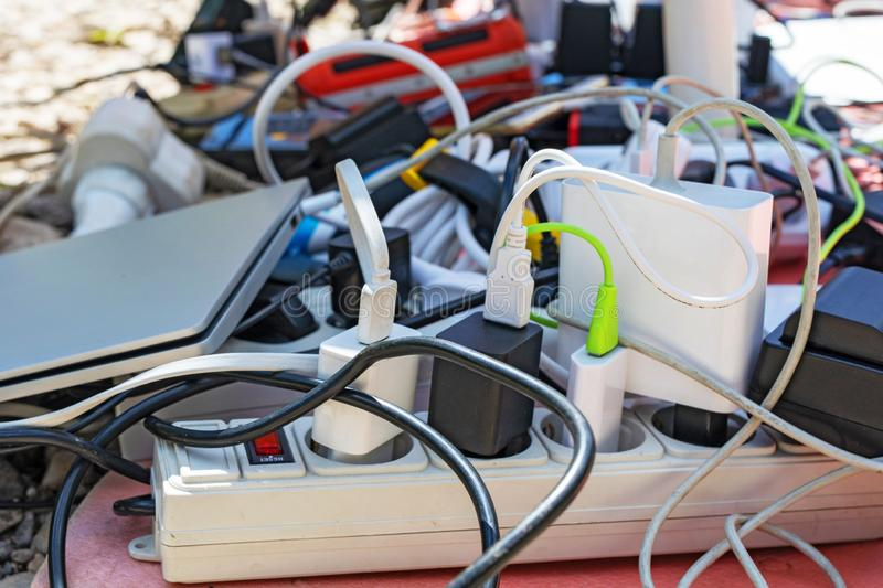 A bunch of charging gadgets, electronic devices, messy wires. Dependence on electricity stock images
