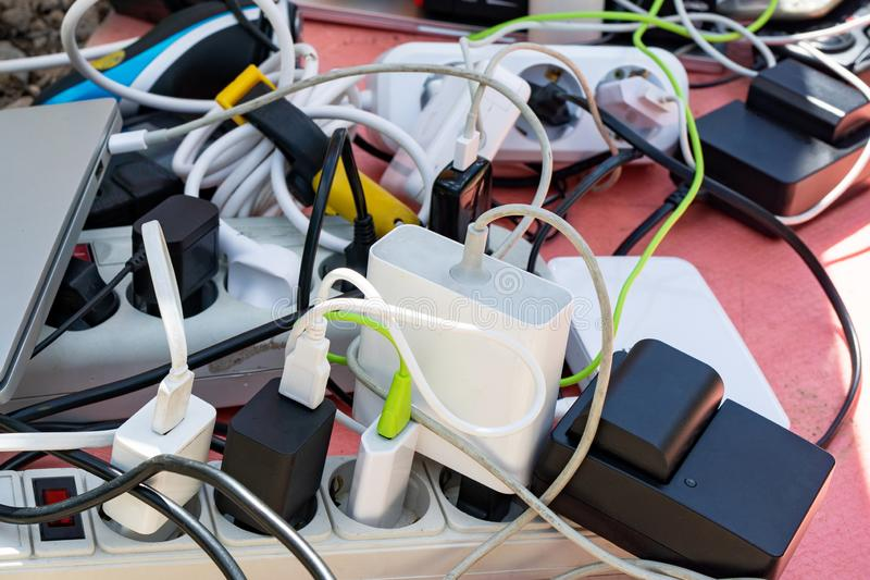 bunch of charging gadgets, electronic devices, messy wires. dependence on electricity stock photography