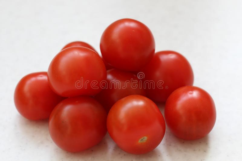 Bunch of Cherry red tomatoes isolated on table stock image