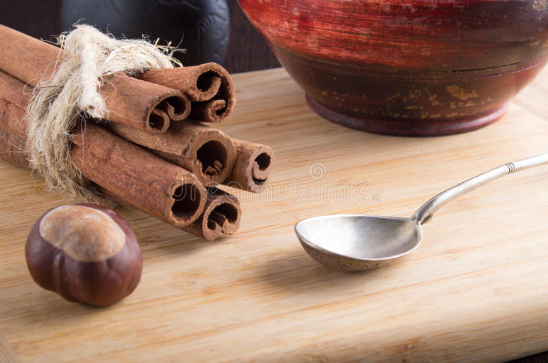 Bunch of cinnamon sticks and vintage silver spoon. Kitchen utensils and spices close-ups. Bunch of cinnamon sticks, vintage silver spoon and a wooden bowl royalty free stock photo