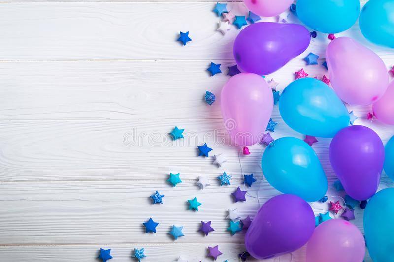 Bunch of colorful party balloons with paper stars on white wooden background royalty free stock photo