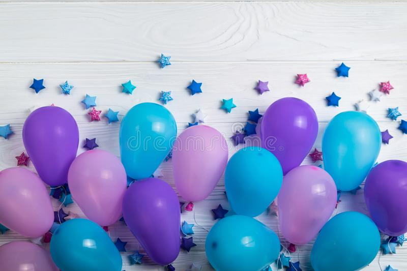 Bunch of colorful party balloons with paper stars on white wooden background stock photo