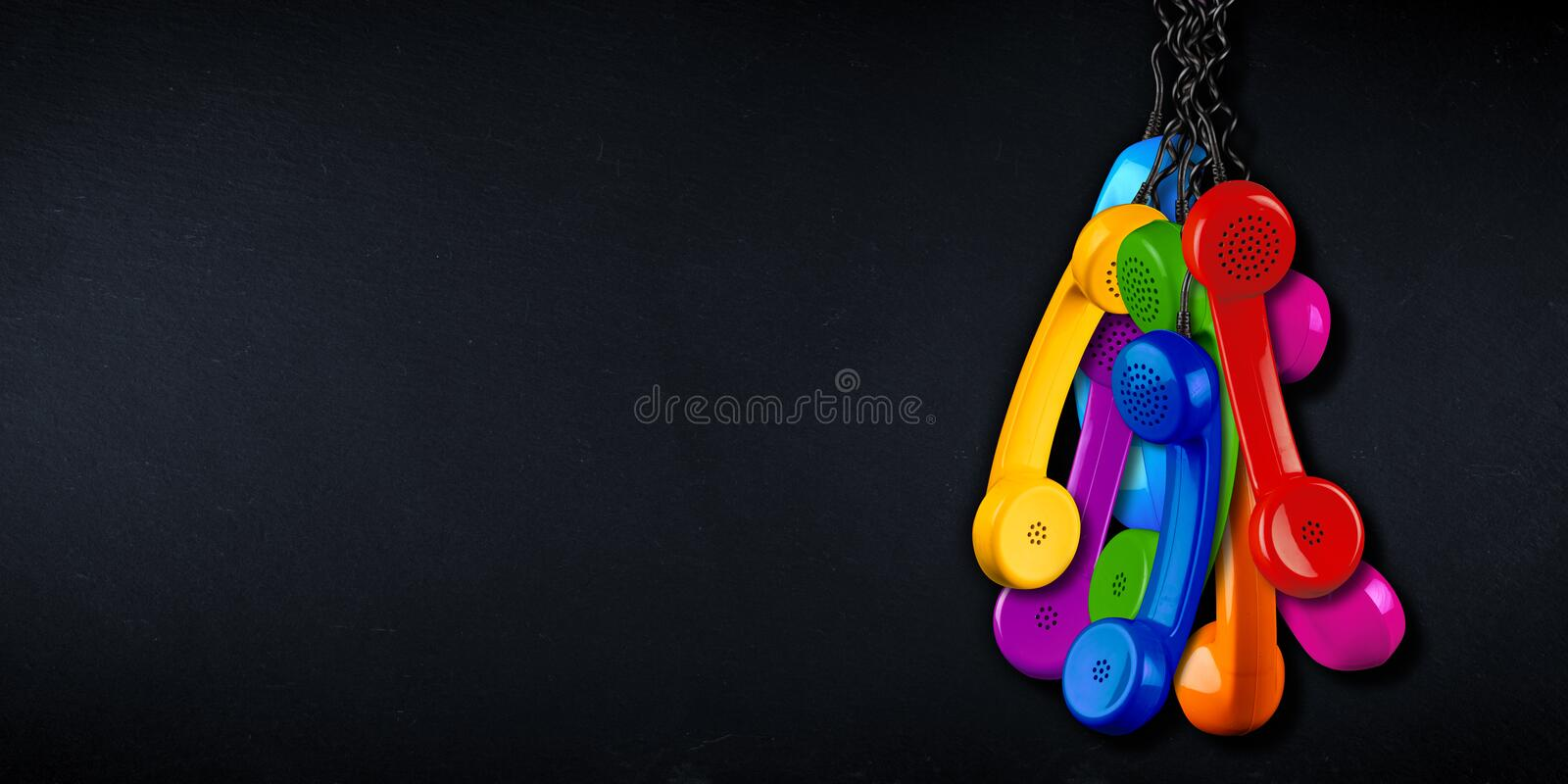 Bunch of colorful rainbow colored old fashioned retro phone reciever with black telephone wire black slate copy space blackboard stock photos