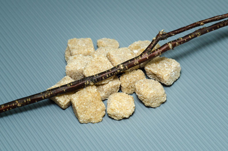 Bunch of cubes brown cane sugar with a branch royalty free stock images