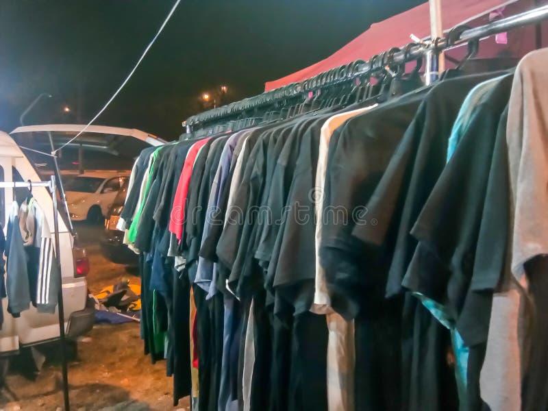 Bunch de camisa de lienzo en el tendedero vender en la venta de coches Boot en Saujana Utama durante la noche fotografía de archivo