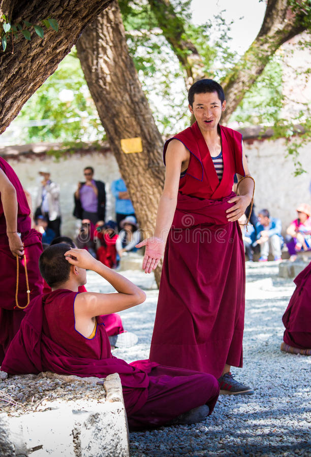 A bunch of debating Tibetan Buddhist monks at Sera Monastery. This event is a famous activity at Sera Monastery in Lhasa, Tibet. A group of Lama are separated stock photography
