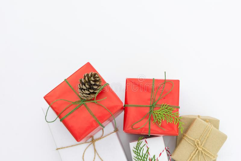 Bunch of different gift boxes wrapped in red craft paper tied with twine green ribbon pine cone juniper twig. White background stock photos
