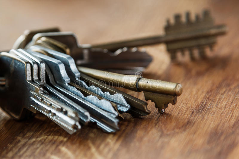 Bunch of different keys. On wooden table stock image