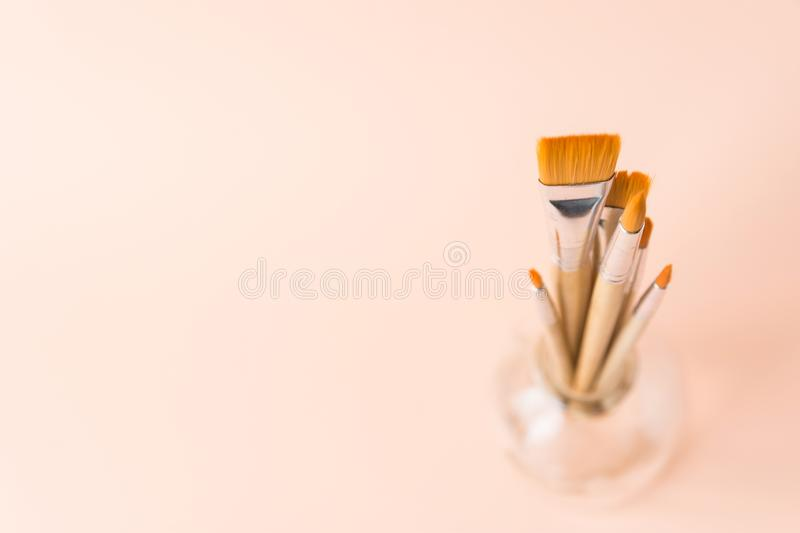 Bunch of different types and sizes of paint brushes in glass jar on light peachy pink background. Arts creativity painting drawing. Education hobby concept stock photos