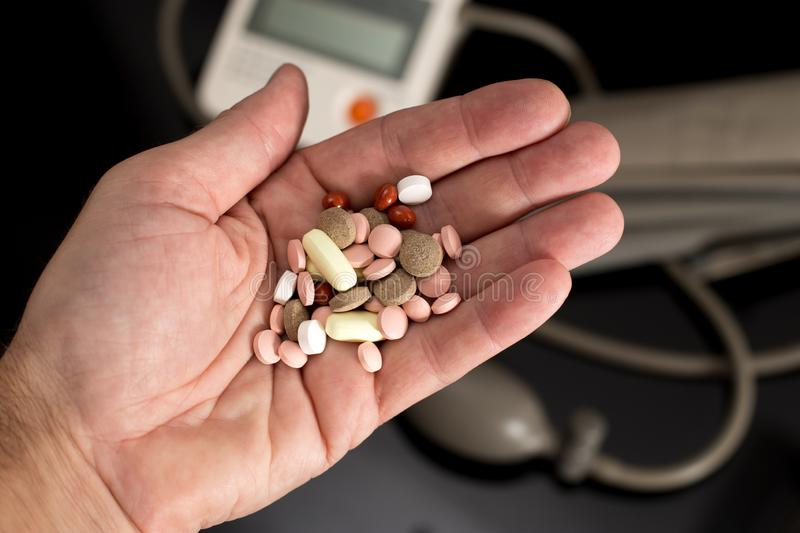 Bunch of drugs in the palm and digital blood pressure monitor royalty free stock photography