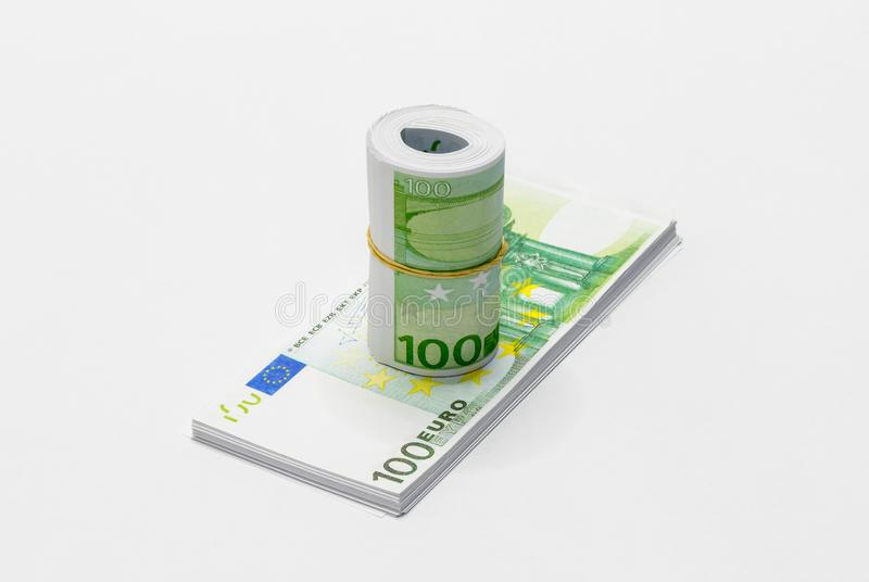 A bunch of European Euro in denominations of 100 Euro notes rolled up and held together with a simple rubber band with one stack o stock images