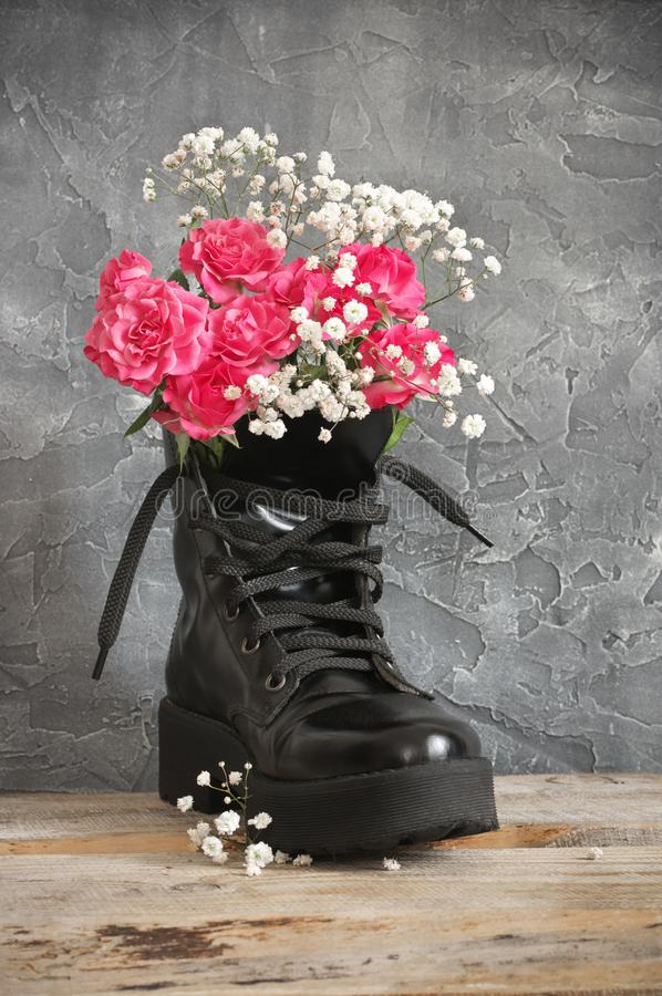 Bunch of flowers in black combat boot. On wood against grey plaster wall stock photo