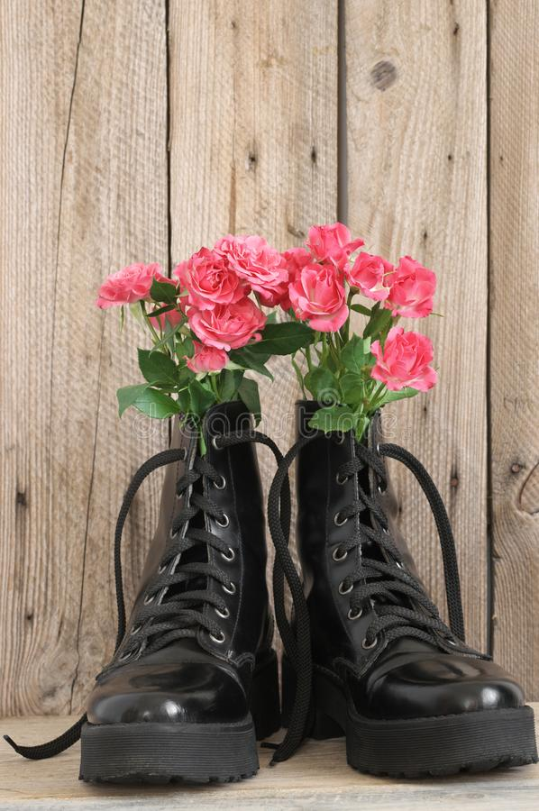 Bunch of flowers in black combat boots. Bunch of pink rose flowers in black combat boots on rough wood background stock image