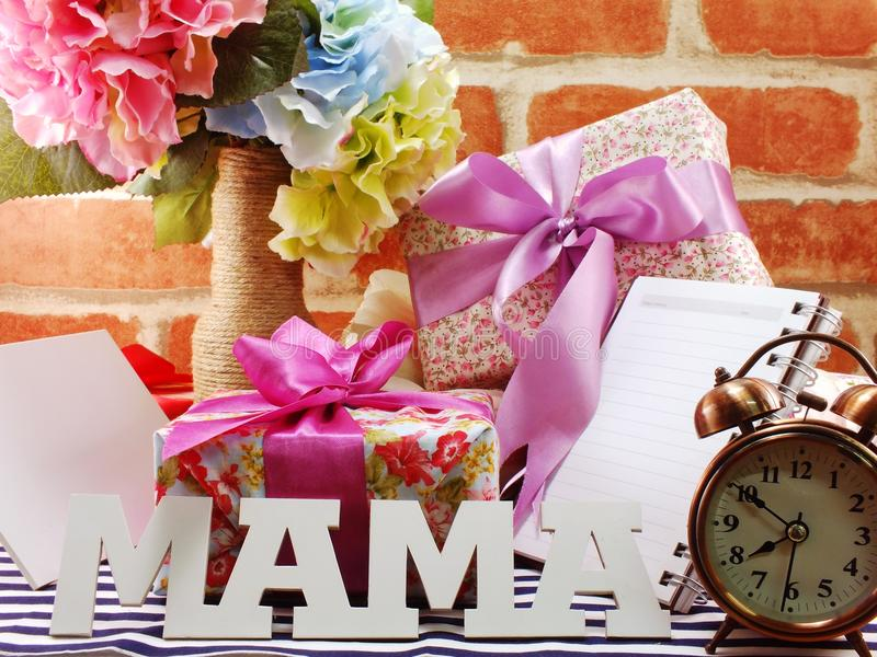 Bunch of flowers with a gift box and word mama on wooden background. Bunch of flower with a gift box and word mama on wooden background royalty free stock photos