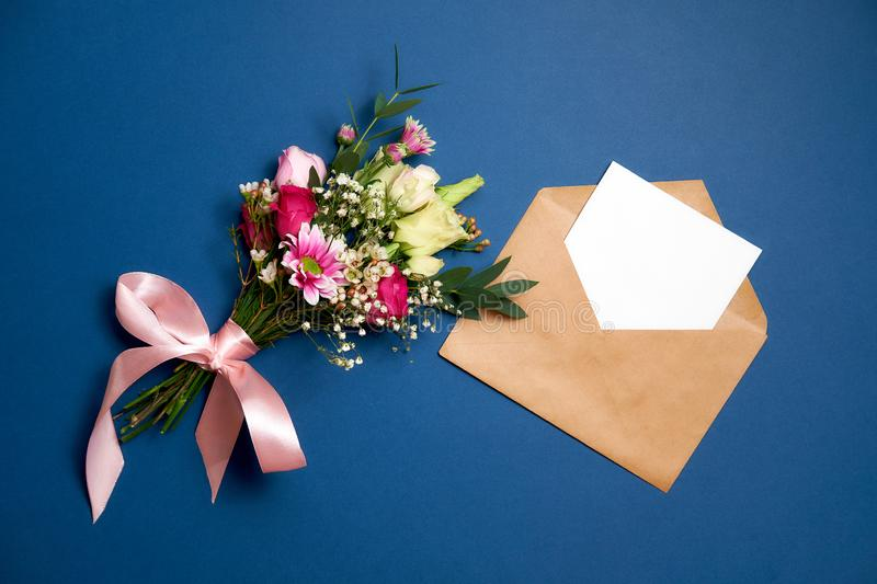 Bunch of flowers kraft paper envelope with blank white letter with copy space lay on blue background. Wedding Marriage or Valentines Day composition: bunch of royalty free stock image