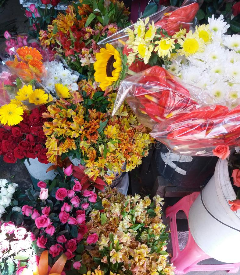 Bunch of flowers namely red, pink, and white roses, sunflower, dandelions and marigolds display on a flower shop royalty free stock images