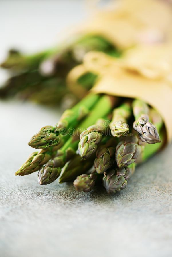 Bunch of fresh asparagus on gray backgrouns. Asparagus on craft paper with packthread. Raw, vegan, vegetarian and clean. Eating concept royalty free stock image