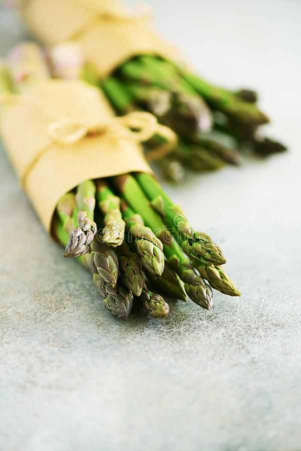 Bunch of fresh asparagus on gray backgrouns. Asparagus on craft paper with packthread. Raw, vegan, vegetarian and clean. Eating concept royalty free stock photos