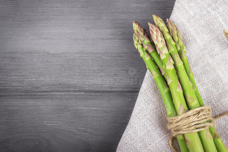 Bunch of fresh asparagus on wooden background. Copy space stock images