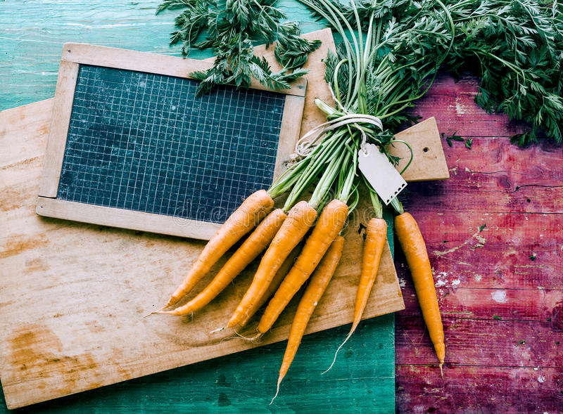 Bunch of Fresh Carrots on Wooden Cutting Board stock images