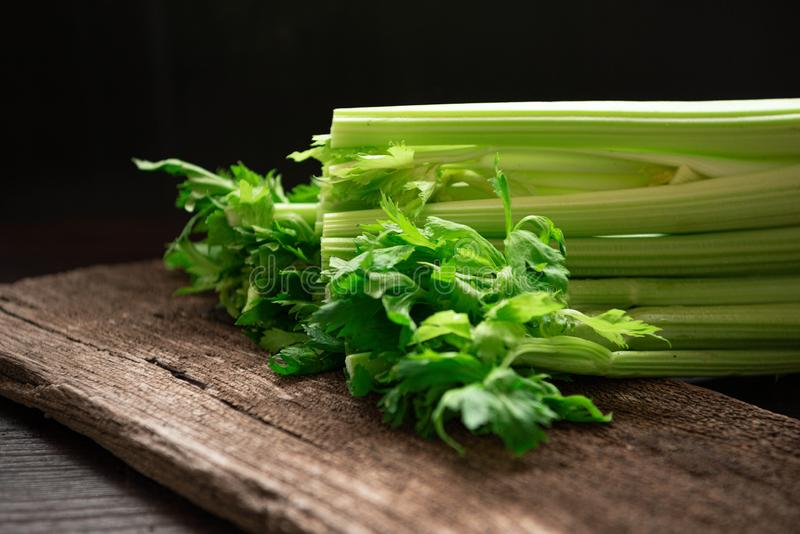Bunch of fresh celery stalk on wooden table with leaves on black background. Food and ingredients  of healthy vegetable. Freshness royalty free stock photo