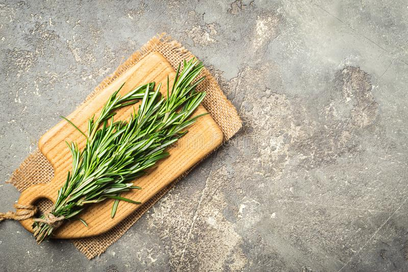 A bunch of fresh fragrant rosemary on a cutting board on a gray concrete background. Copy space. Flat layout. stock photo