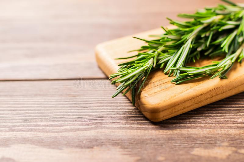 A bunch of fresh fragrant rosemary on a cutting board on a wooden background. Copy space. Selective focus. royalty free stock photos