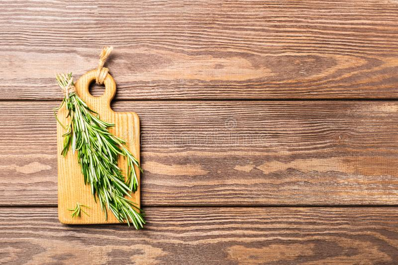 A bunch of fresh fragrant rosemary on a cutting board on a wooden background. Copy space. View from above. Flat layout. stock photo