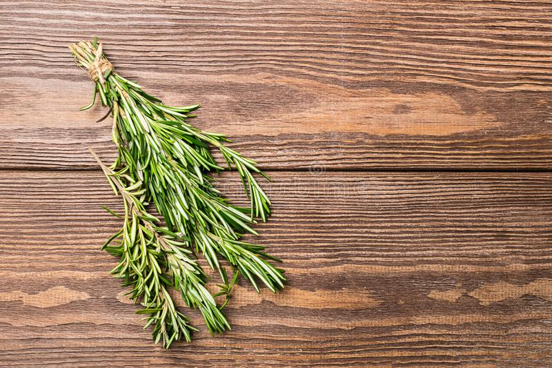 A bunch of fresh fragrant rosemary on a wooden brown background. Copy space. Ploskoy layout. royalty free stock photography