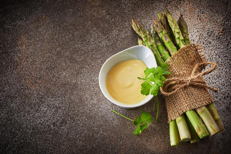 Bunch of fresh green asparagus and bowl of sauce stock images