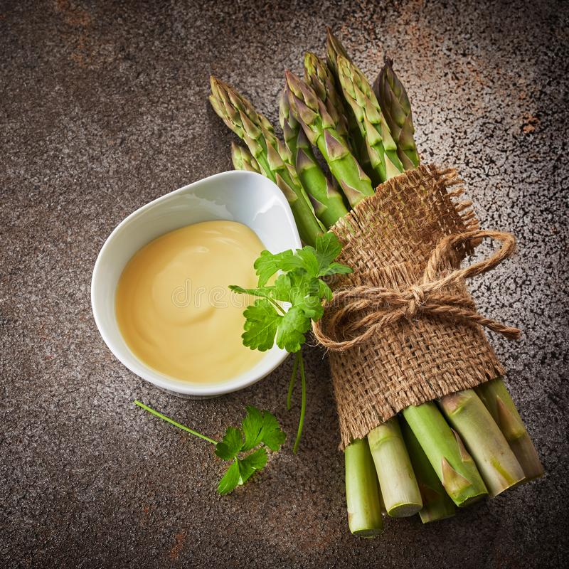 Bunch of fresh green asparagus with mayonnaise royalty free stock photo