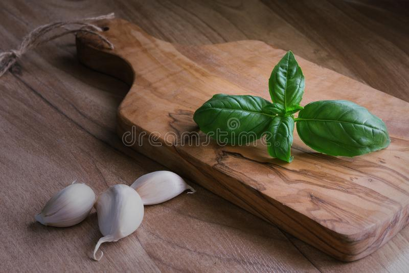 Bunch of fresh organic basil and garlic in olive cutting board on rustic wooden background stock images