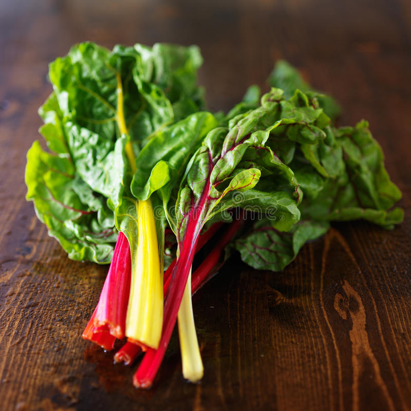 Bunch of fresh rainbow chard. On wooden table royalty free stock image