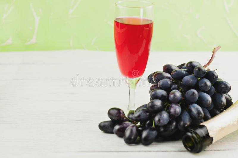 Bunch of fresh ripe blue grapes near transparent and fragile glass full of wine and one opened bottle on wooden rustic white p royalty free stock images