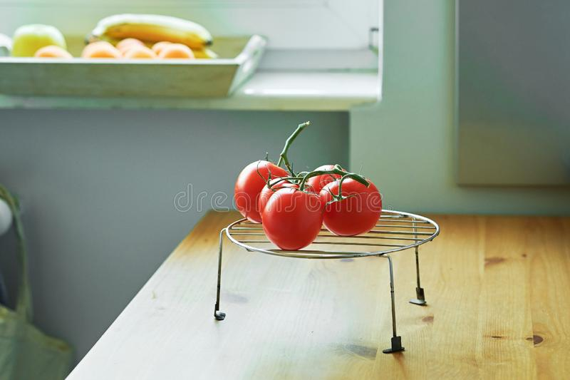 Bunch of fresh ripe tomatoes on a metal stand on a wooden table stock image