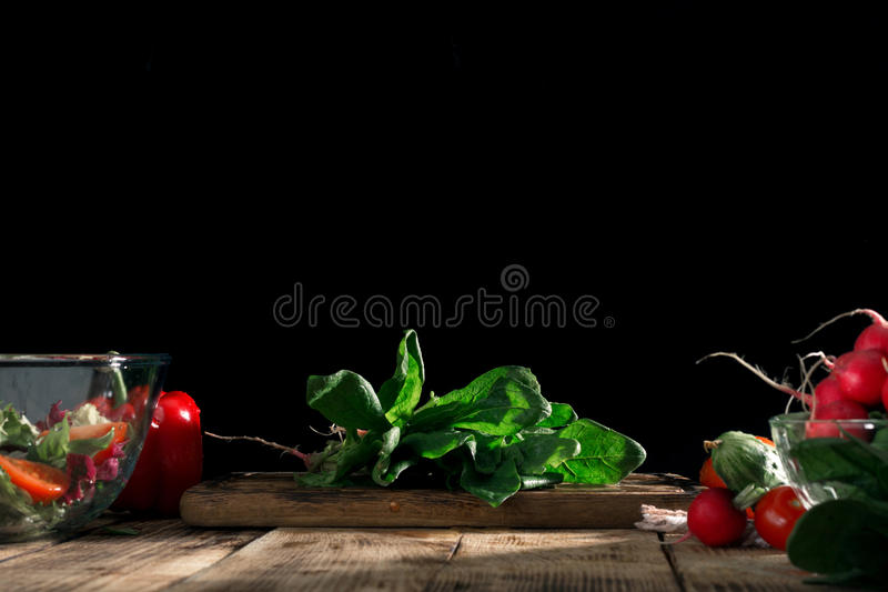 Bunch of fresh spinach with various vegetables on wooden table stock photography