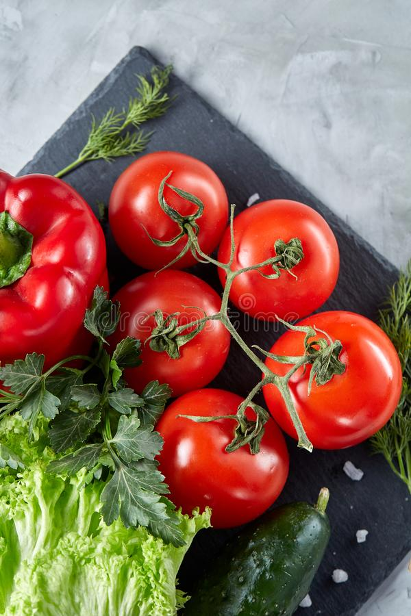 Bunch of fresh tomatoes with green leaves on stony board over white background, top view, close-up, selective focus stock image