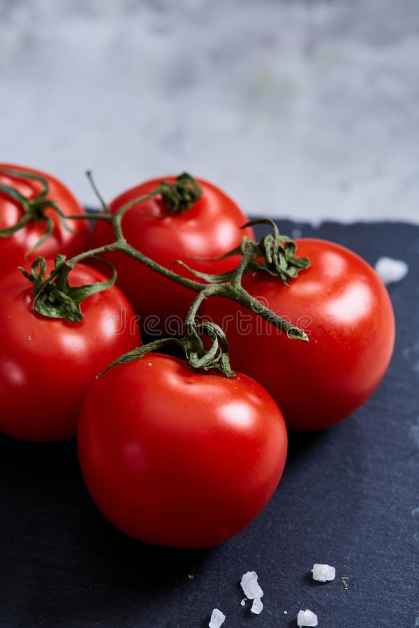 Bunch of fresh tomatoes with green leaves on stony board over white background, top view, close-up, selective focus stock photos