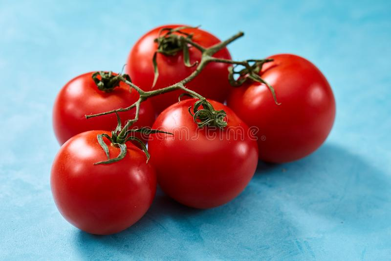 Bunch of fresh tomatoes with green leaves on blue background, top view, close-up, selective focus stock photos