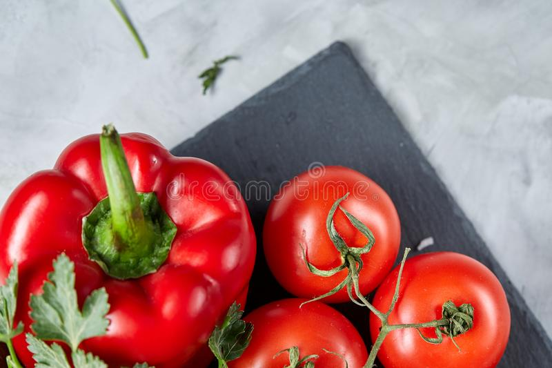 Bunch of fresh tomatoes with green leaves on stony board over white background, top view, close-up, selective focus royalty free stock images