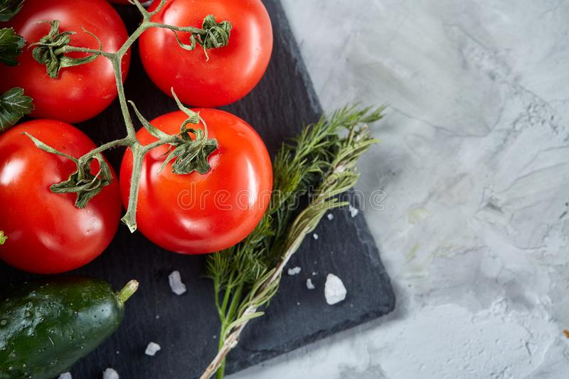 Bunch of fresh tomatoes with green leaves on stony board over white background, top view, close-up, selective focus royalty free stock photography