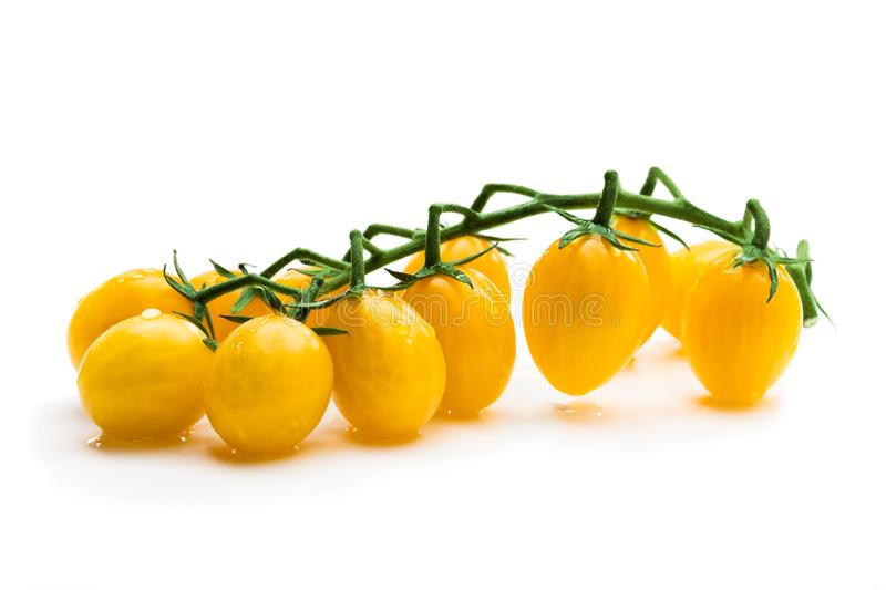 Bunch of fresh yellow cherry tomatoes with water drops isolated on white royalty free stock photos