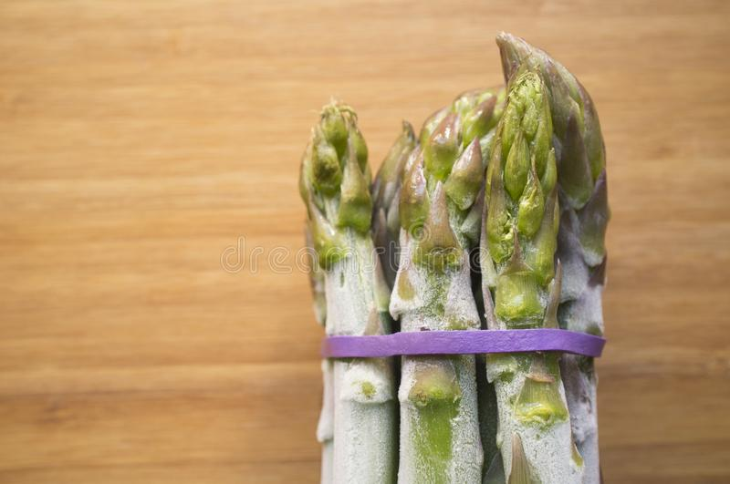Bunch of frozen wild asparagus tied with rubber tape from ecological agricuture over wooden background stock photos
