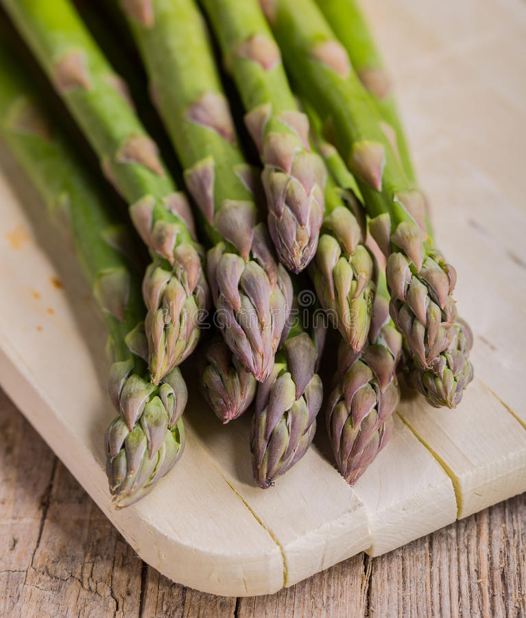 Bunch of green asparagus on cutting board royalty free stock photo