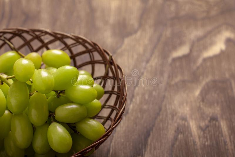 Bunch of green grapes in the basket, fruits of autumn, a symbol of abundance on rustic wood background with copy space, top view,. Close-up royalty free stock images