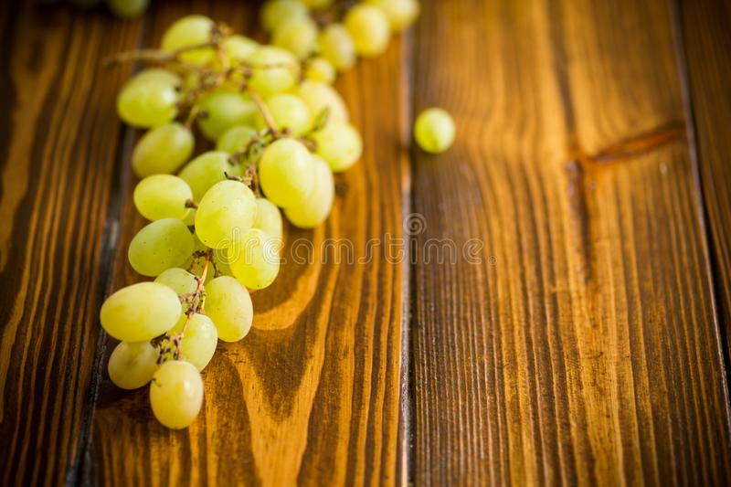 Bunch of green grapes on a dark wooden table stock photos