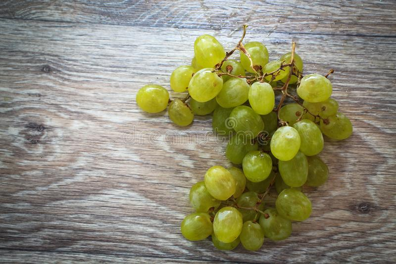 Bunch of green grapes on a light wooden tabletop royalty free stock images