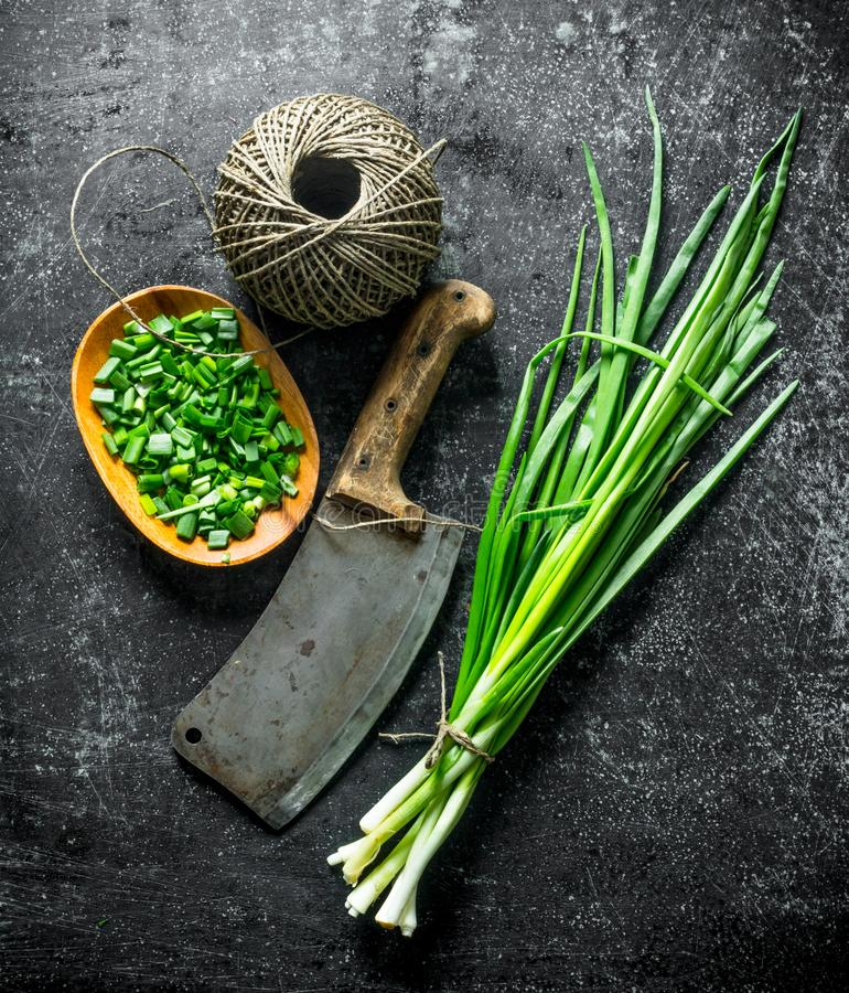 Bunch of green onion with chopped green onion on a plate, old knife and twine. On dark rustic background stock photography