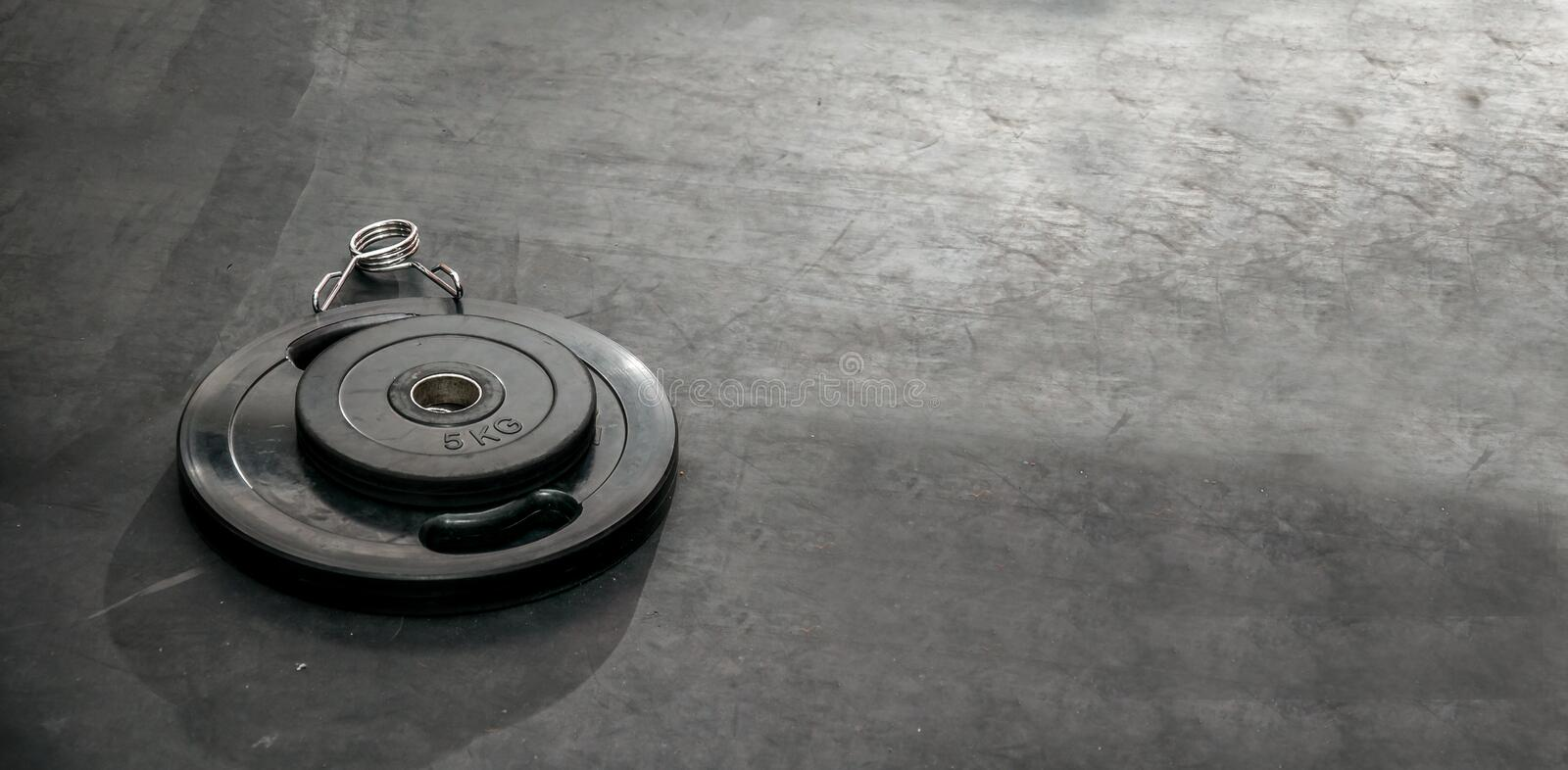 Bunch of heavy black barbell weight plates on the gym floor prepared for hard core fitness workout strong contrast dark image. Gym bodybuilding workout concept stock photo